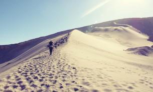 Climbing the sandboarding dune in San Pedro de Atacama