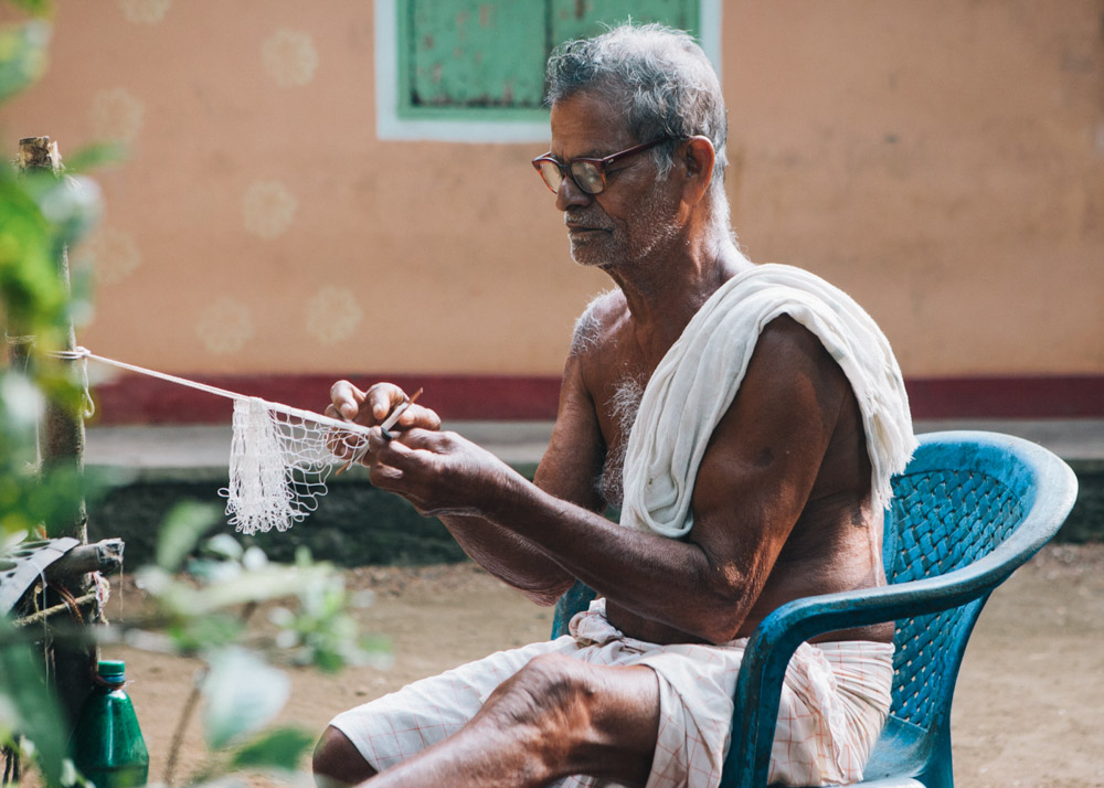 Man sewing fishing net in Kerala backwaters